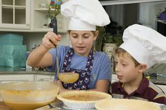 Baking a pie 5. Brother and sister baking a pie for the holidays measuring ingredients Royalty Free Stock Photos