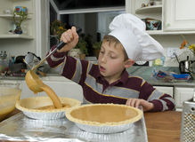 Baking a pie 6. Young boy baking a pie for the holidays pouring ingredients into a pie shell with a ladle Stock Images