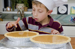 Baking a pie 7. Young boy baking a pie for the holidays taking a sample with finger Royalty Free Stock Photos