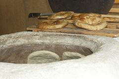 Baking pita bread in a stone oven Royalty Free Stock Photography