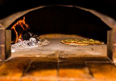 Baking pizza in the brick wood oven with firewood and flame. It's homemade and original formula for cooking delicious pizza. It royalty free stock photo
