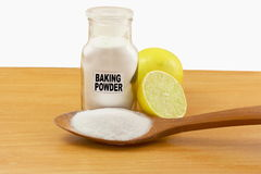 Baking powder in glass bottle and wooden spoon with lemon fruit Stock Photos