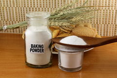 Baking powder in a glass jar  and wooden spoon with cookie and bread Royalty Free Stock Images