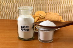 Baking powder in a glass jar  and wooden spoon with cookie and bread Stock Image