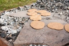 Baking prehistoric bread on stones. Baking prehistoric bread on some stones, ancient tradition performed outdoors Stock Images