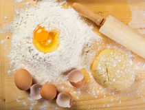 Baking preparation: eggs, flour, rolling pin on a board . Royalty Free Stock Image