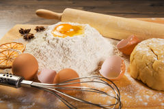 Baking preparation: eggs, flour, rolling pin, spices on a board Stock Photos