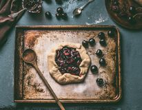 Baking preparation of homemade open cherry pie or galette on aged baking tray background with wooden spoon Stock Photography