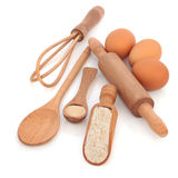 Baking Products. Baking equipment and ingredients, with wholegrain flour, yeast and eggs, with rustic natural wooden spoons, scoop, whisk and rolling pin Stock Photo