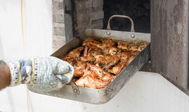 Baking rabbit in a stone oven Royalty Free Stock Image