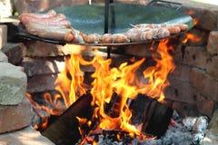 Baking sausages at the campfire Royalty Free Stock Photo