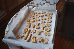 On a baking sheet with baking paper spread out blanks figured cookies. On a baking sheet with baking paper spread out blanks figured Christmas shortbread Stock Photos