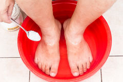 Baking soda being used as feet bath at home. Royalty Free Stock Image