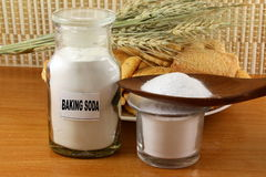 Baking soda in a bottle glass jar and wooden spoon with cookie and bread Stock Photo