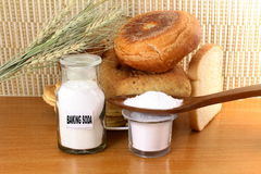 Baking soda in a bottle glass jar and wooden spoon with cookie and bread Stock Images