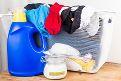 Baking soda with detergent and pile of dirty laundry. Royalty Free Stock Photo