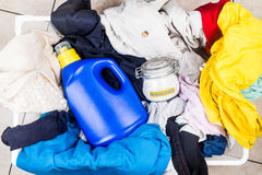 Baking soda with detergent and pile of dirty laundry. Royalty Free Stock Photography