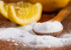 Baking soda (sodium bicarbonate) in a wooden spoon. And lemon Royalty Free Stock Photo
