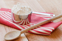 Baking spoon and measuring cup. A wooden baking spoon and a silver measuring cup filled with flour rest on a red striped towel a top a wooden farm table Stock Photography