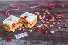 Baking Surprise Cookies with topping and icing on wooden background with pink heart stock photography