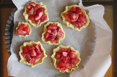 Baking tartlets with strawberries royalty free stock images