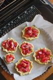 Baking tartlets with strawberries royalty free stock photography