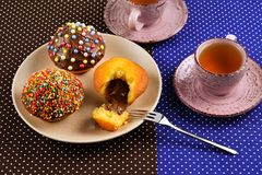 Two cups of tea with cupcakes and chocolate with a multicolored powder on the table. stock image