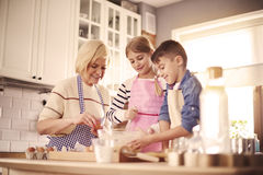 Baking time. Three intent chefs in the domestic kitchen royalty free stock photos