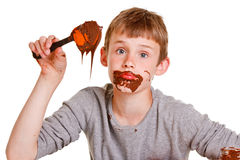 Baking time with a young boy eating the chocolate Stock Photo