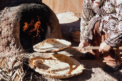Baking traditional bread in a natural clay oven. Royalty Free Stock Photo