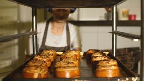 Baking tray with cinnamon buns. Baker takes a tray of scones stock video