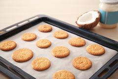 Baking tray with cookies and coconut on table