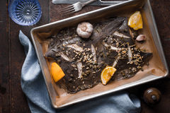 Baking tray with flounder and seasoning on the stone background top view Stock Photos