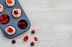Baking tray with fruit and cupcakes on a white wooden background stock photos