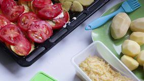 On a baking tray are laid with layers of potatoes, zucchini and tomatoes.