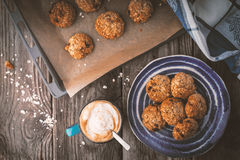 Baking tray and a plate of oatmeal cookies on the wooden table Royalty Free Stock Photography