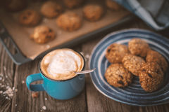Baking tray and a plate of oatmeal cookies on the wooden table Stock Photo