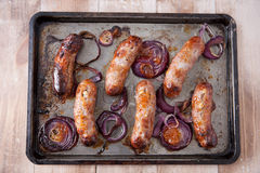 Baking tray with six baked pork and apple sausages Stock Photography