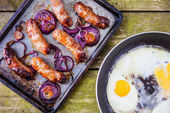 Baking tray with six baked pork and apple sausages Stock Photos