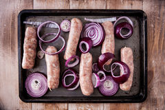 Baking tray with six raw pork and apple sausages Stock Photography