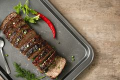 Baking tray with sliced tasty turkey meatloaf. On table royalty free stock photos