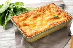 Baking tray with spinach lasagna. On table royalty free stock photo