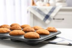 Baking tray with tasty cupcakes on table Stock Photo