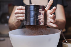 Baking. Two hands sifting cacao into a bowl Stock Images