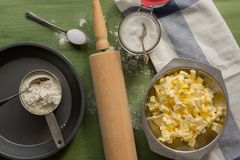 Baking utensils, flour, sugar, butter on green wooden surface. Several types of baking utensils arranged on a green wooden surface with flour in a cub, sugar in Stock Photos