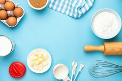 Baking utensils and ingredients on blue background