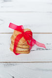 Baking Valentines Day. Some cookies hearts tied with red ribbon on white wooden table Royalty Free Stock Photos