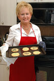 Baking woman. A senior woman wearing an apron and holding sugar cookies fresh from the oven Royalty Free Stock Image
