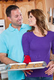 Baking woman. A beautiful woman baking cookies with her husband in the kitchen Stock Photography