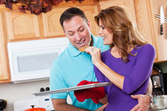 Baking woman. A beautiful woman baking cookies with her husband in the kitchen Royalty Free Stock Photography